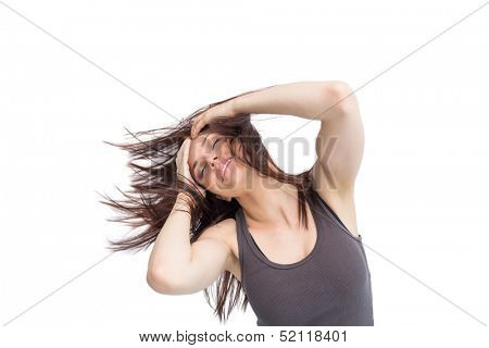 Pretty young brunette on white background tossing her hair