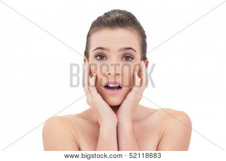 Disappointed natural brown haired model touching her face on white background