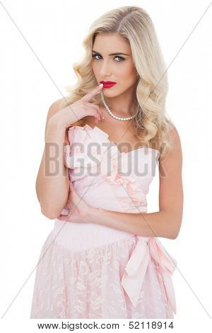 Contemplative blonde model in pink dress posing a finger on the mouth on white background