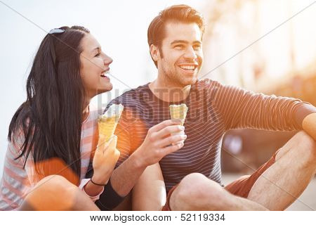 romantic couple eating ice cream at park