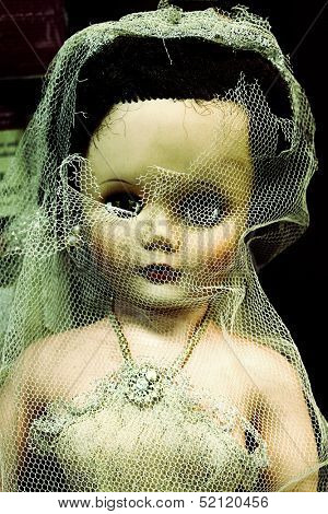 Old doll in ripped wedding outfit