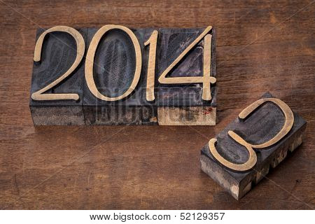 new year 2014 replacing old year 2013 - letterpress wood type on a grunge wooden surface