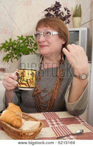 Frau mit einer Tasse in der Küche