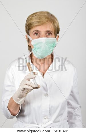 Senior Woman Doctor With Syringe And Protective Mask