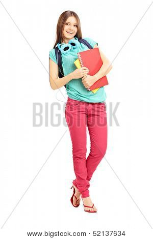 Full length portrait of a smiling female with schoolbag and headphones looking at camera and leaning against a wall