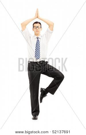 Full length portrait of a young businessman meditating isolated on white background