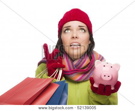 Stressed Mixed Race Woman Wearing Winter Clothing Looking Up Holding Shopping Bags and Piggy Bank Isolated on White Background.