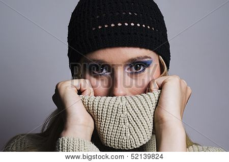 blonde woman covering her face with turtleneck