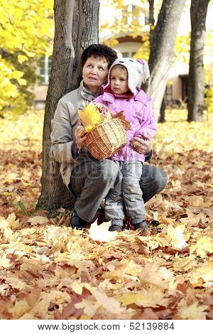 Grandmother and grandkid in the autumn park