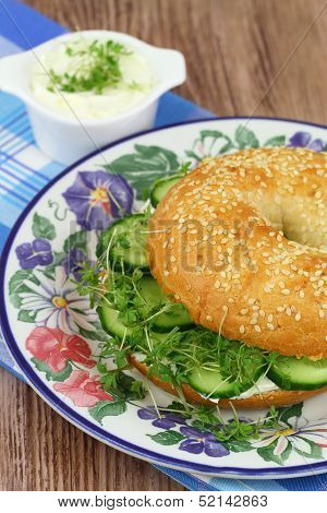 Bagel with cream cheese, cucumber and watercress, close up