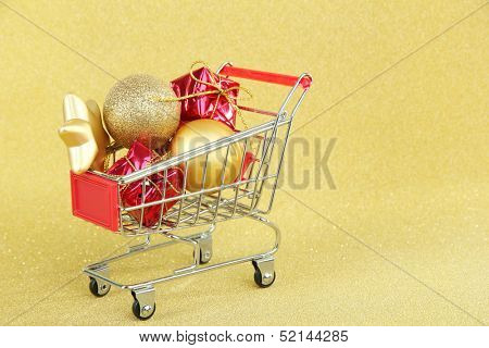 Christmas gifts in shopping trolley, on golden shiny background