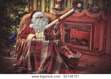 Santa Claus with a list of Christmas presents sitting in a comfortable chair near the fireplace at home.