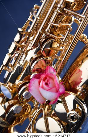 Gold Saxophone And Pink Rose On Blue