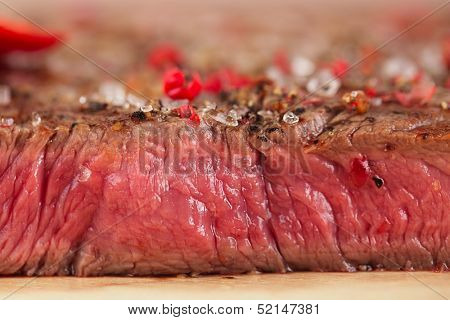 Beef steak on a wooden board and table
