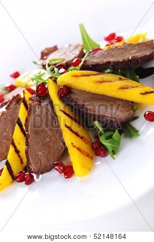 Salad with duck fillet and grilled mango on white background.