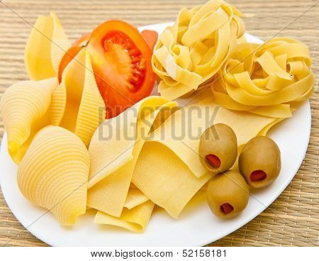 Different dry pasta with olives and tomat on a plate