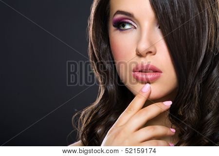 Portrait of beautiful girl touching her face with bright pink make-up on grey background. Concept of beauty and fashion