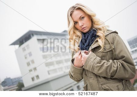 Serious attractive blonde posing outdoors on urban background