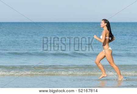 Sensual Brunette Running On The Beach. Place For Text.
