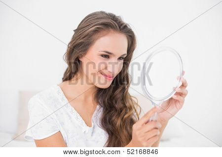 Grinning attractive brunette looking at mirror in bright bedroom