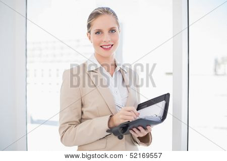 Smiling blonde businesswoman holding datebook standing in bright office