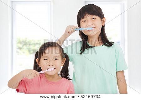 Zwei glückliche kleine Mädchen, die ihre Zähne putzen
