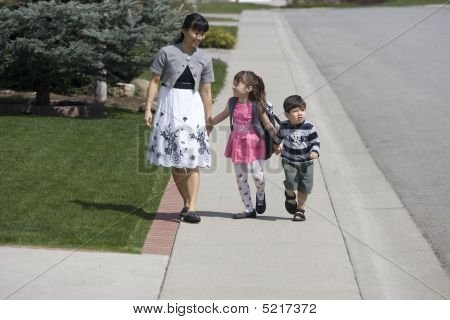 Mother And Tow Kids Taking A Walk.