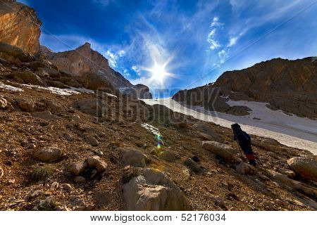Weary Hiker Ascent To Mountain Pass In Evening