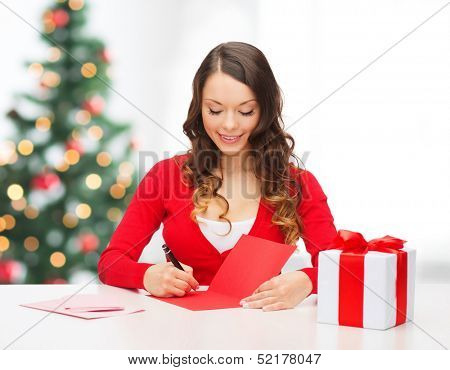 christmas, x-mas, valentine's day, celebration concept - smiling woman in red clothes with gift box and postcard