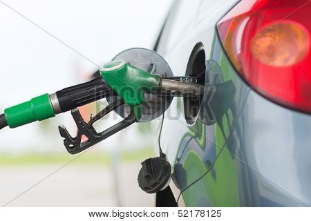 transportation and ownership concept - pumping gasoline fuel in car at gas station