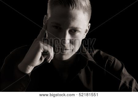 Low-key close up portrait of young seductive man in dark shirt looking straight, black and white, isolated on black background.