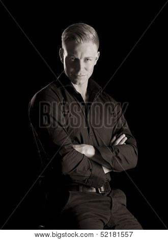 Black and white portrait of confident seductive man in dark shirt looking straight, low-key, isolated on black background.