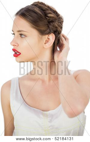 Puzzled model in white dress touching her hair and looking away on white background