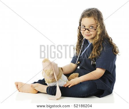 A pretty elementary girl in scrubs looking over her glasses as she bandage's her teddy bear's head.  On a white background.