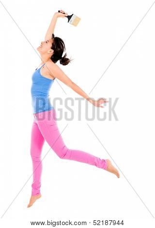 Happy woman painting with a brush and jumping - isolated over white