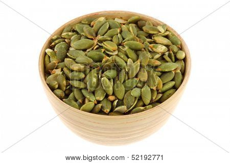 A bowl of Roasted and Salted Pumpkin seeds, isolated on white background