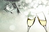 stock photo of champagne glasses  - Glasses with champagne against fireworks and clock close to midnight - JPG