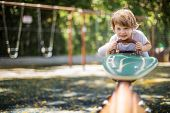 stock photo of seesaw  - Happy child playing seesawing in playground - JPG