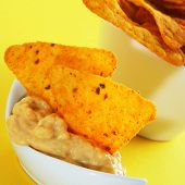 a bowl with tortilla chips and nacho cheese on a yellow background