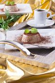 stock photo of panna  - Sweet italian dessert Panna cotta with a cocoa powder and mint on the top on a white plate - JPG