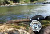 picture of fly rod  - Close up mayfly and fishing rod on the stone near the river - JPG