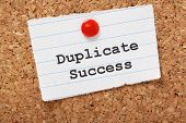 stock photo of jargon  - Duplicate Success typed onto a scrap of lined paper and pinned to a cork notice board - JPG