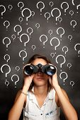 stock photo of interrogation  - young woman using binoculars in front of chalkboard with interrogation symbols - JPG