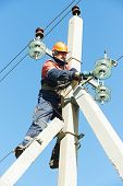 foto of lineman  - Electrician lineman repairman worker at climbing work on electric post power pole - JPG