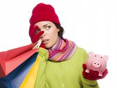 Concerned Expressive Mixed Race Woman Wearing Winter Clothing Holding Shopping Bags and Piggy Bank I