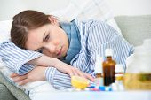 image of sneezing  - Sick woman lying in bed with high fever - JPG