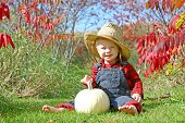 image of baby cowboy  - a cute smiling baby boy is sitting outside in the grass with a white pumpkin on a sunny autumn day wearing a straw hat flannel and overalls like a little farmer - JPG