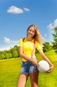 stock photo of 13 year old  - Happy and smiling 13 years old girl with long blond hair standing in the grass with the ball in the park on sunny summer day - JPG