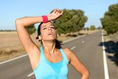stock photo of sportswear  - Tired runner sweating after running hard on countryside road - JPG