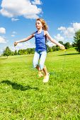 stock photo of skipping rope  - Beautiful girl with skipping rope jumping in the park on green grass field on sunny summer day